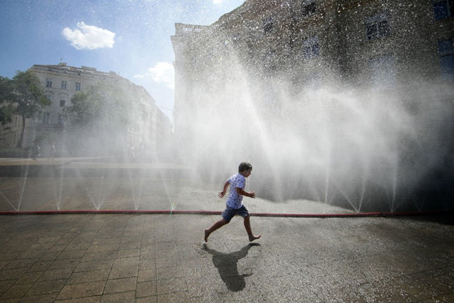 Một em bé giải nhiệt tại cụm vòi phun nước ở Vienna, Áo